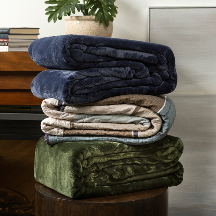 Blankets and Quilts piled together on shelf
